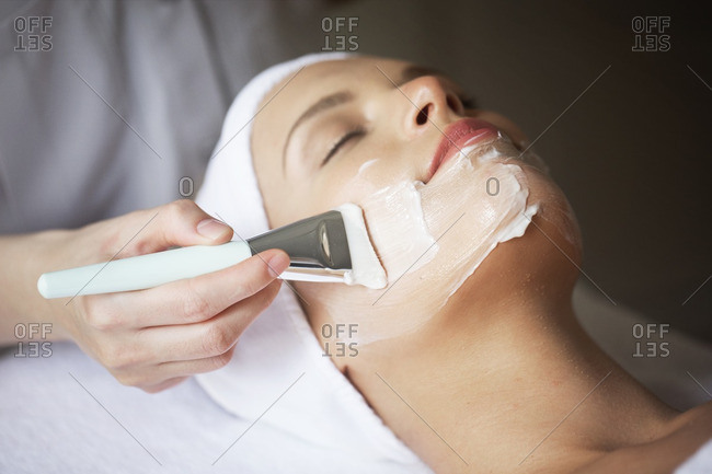 Female therapist applying facial mask on woman\'s face in spa