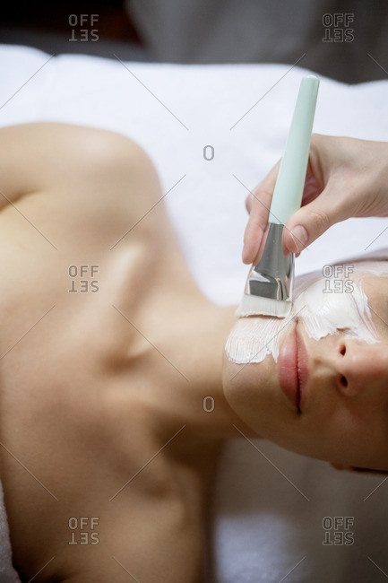 Overhead view of cream being applied on woman\'s face in spa