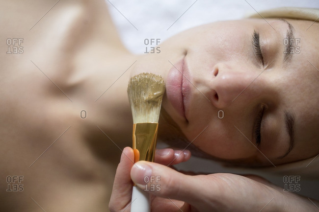 Overhead view of facial mask being applied on woman\'s face in spa