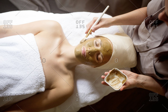 Overhead view of female therapist applying facial mask on woman\'s face in spa