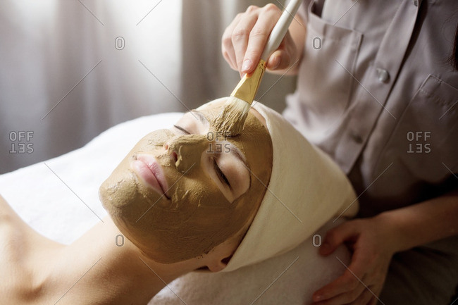 Therapist applying facial mask on woman\'s face in spa