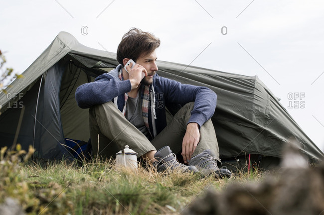 Man answering smart phone outside tent on hill against clear sky