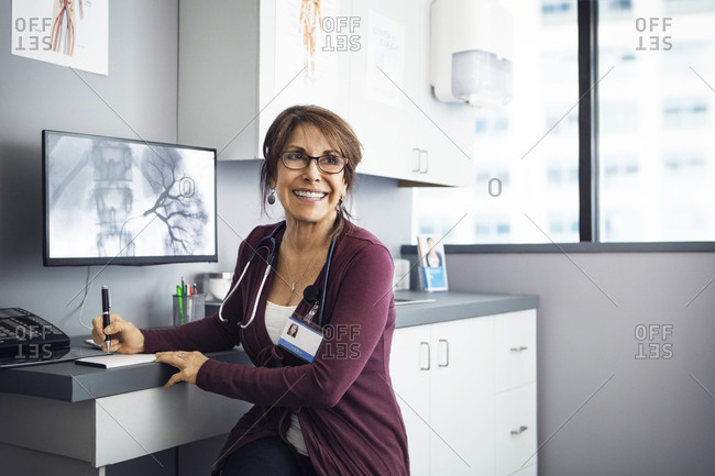 Happy female doctor sitting at desk in clinic