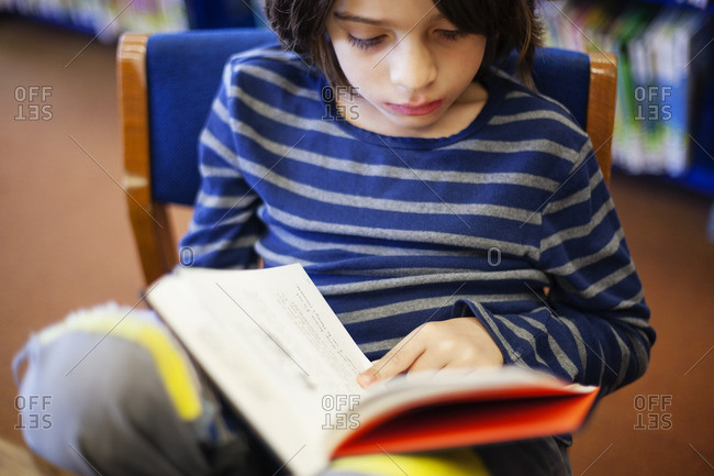 High angle view of boy reading book in library