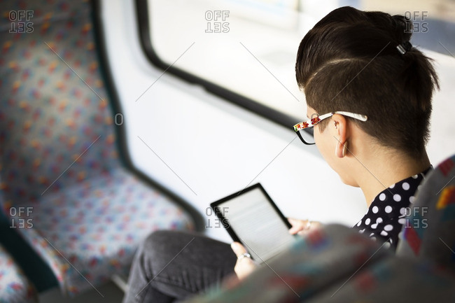 Rear view of woman using e-book in train