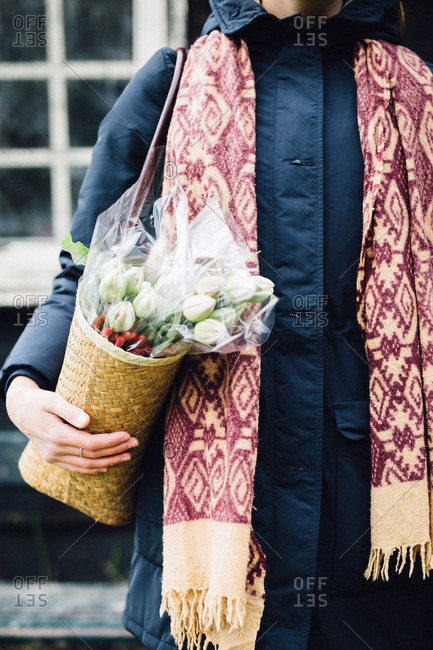 Woman carrying shoulder bag containing bouquet of flowers