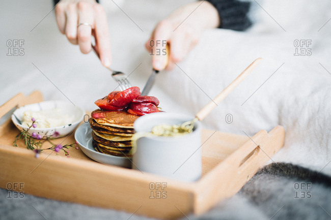 Person cutting into pancake breakfast on bed