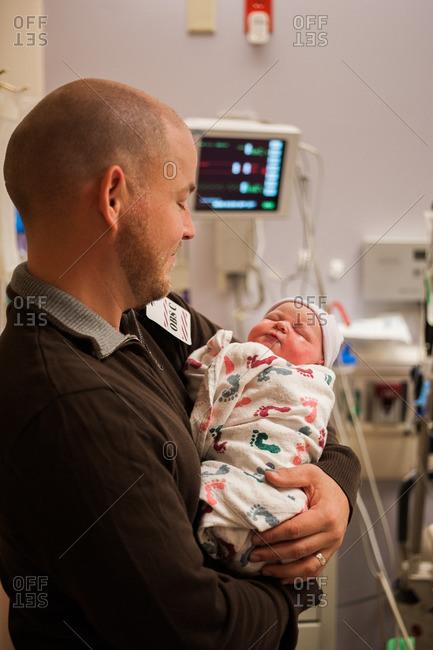 Man cradling newborn in hospital