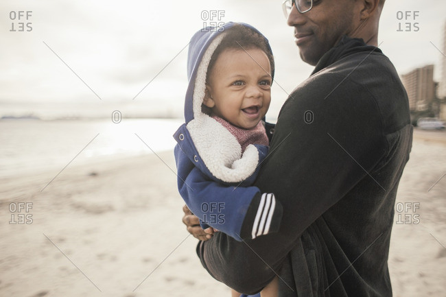 Baby in dad's arms at beach