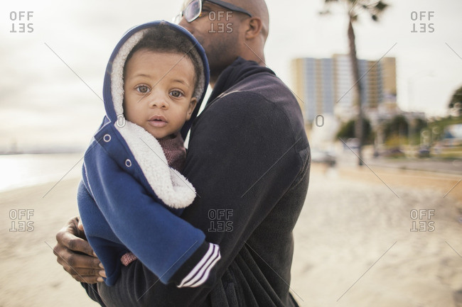 Baby in father's arms at beach
