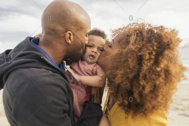 Parents kissing baby at beach