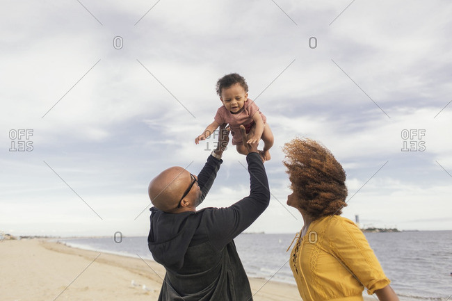 Father tossing girl at the beach