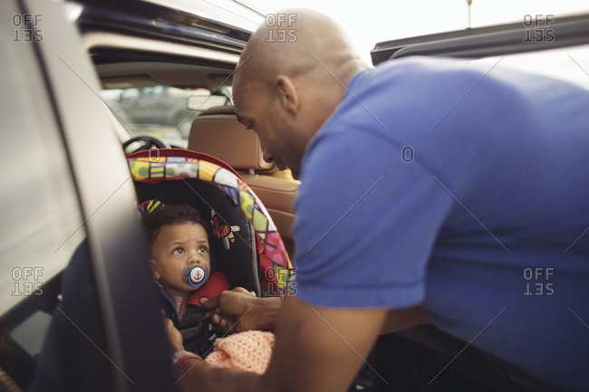 Father fastening baby into car seat