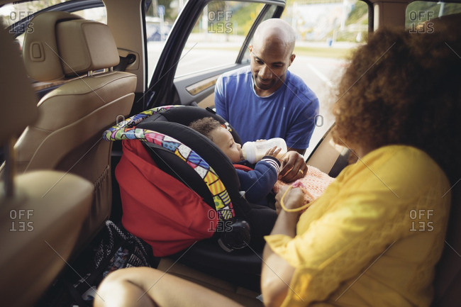 Parents putting baby in car seat
