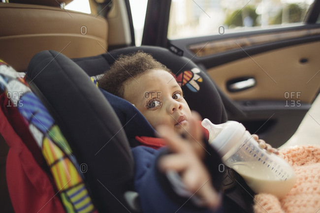 Baby in a car seat holding bottle