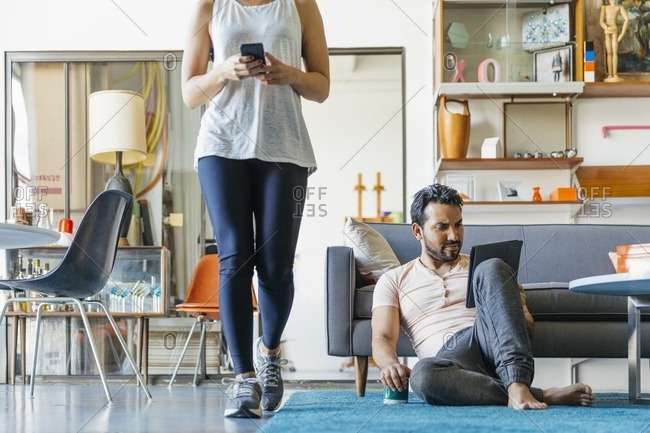 Young couple at home with devices