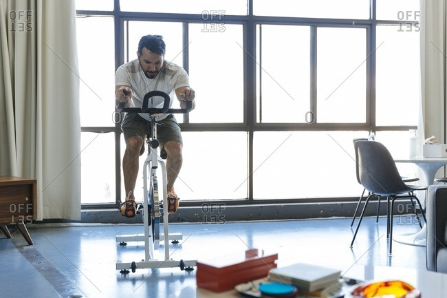 Man riding stationary bicycle in loft apartment