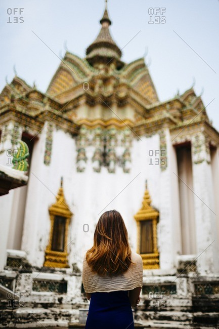 Woman visiting Buddhist complex, Thailand