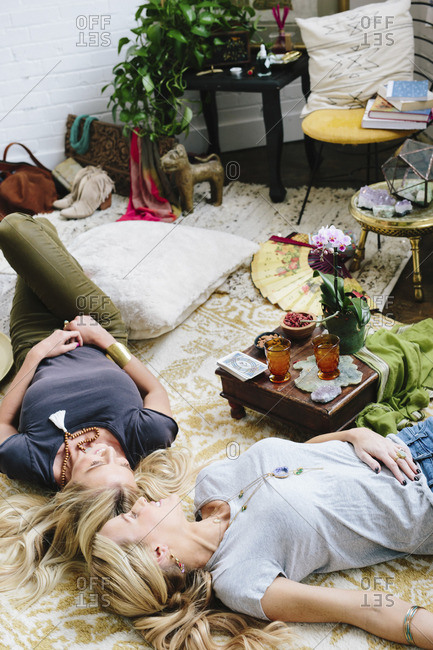Two women lying on the floor of a room strewn with cushions and personal possessions