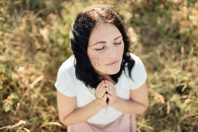 Portrait of a woman with eyes shut praying in a field