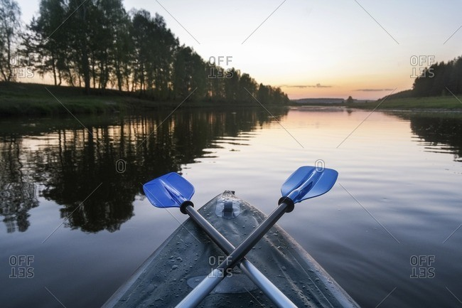 Cropped image of kayak with oars on lake during sunset