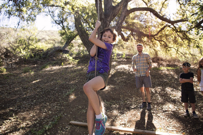 Family looking at girl hanging from rope swing in forest