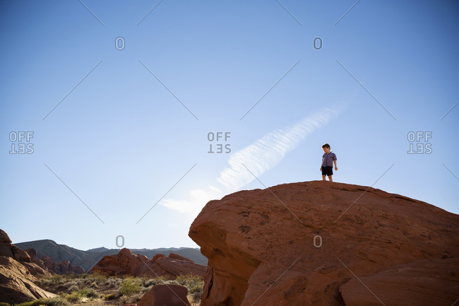 Low angle view of boy standing on cliff at Valley of Fire State Park against blue sky
