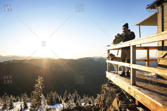 Man standing with dog on balcony at tourist resort during winter