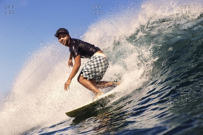 Young man surfing in sea against sky