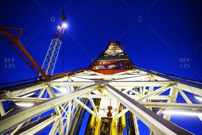 Low angle view of tower in oil rig against clear blue sky at dusk