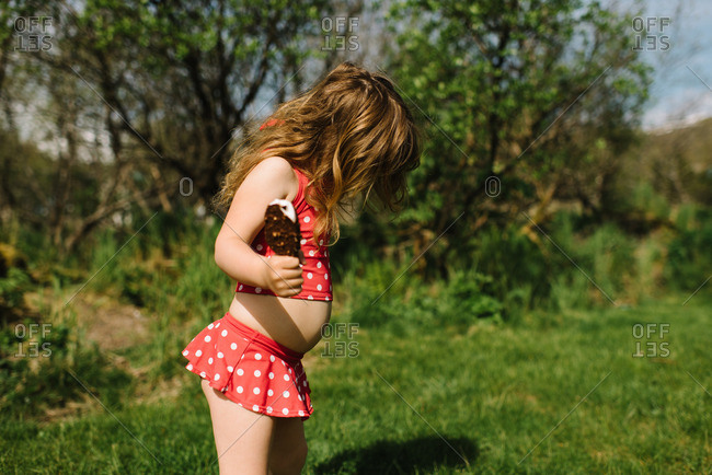 Young girl in a polka dot bathing suit holding an ice cream bar