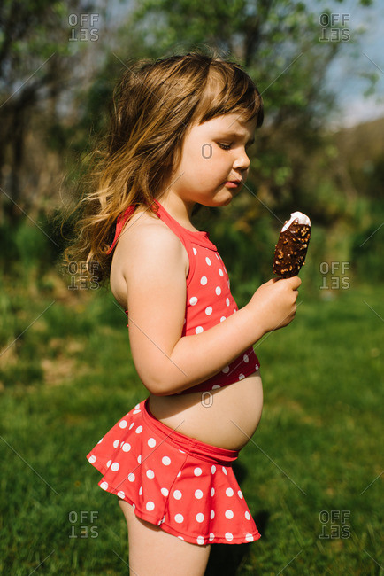 Young girl in a polka dot bathing suit eating an ice cream bar