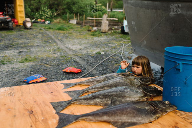 Girl standing outside next to a table lined with freshly caught fish