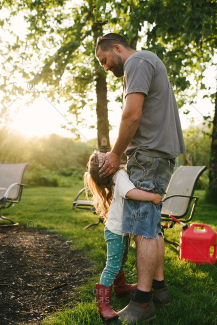 Girl standing outside in her yard hugging her father\'s legs
