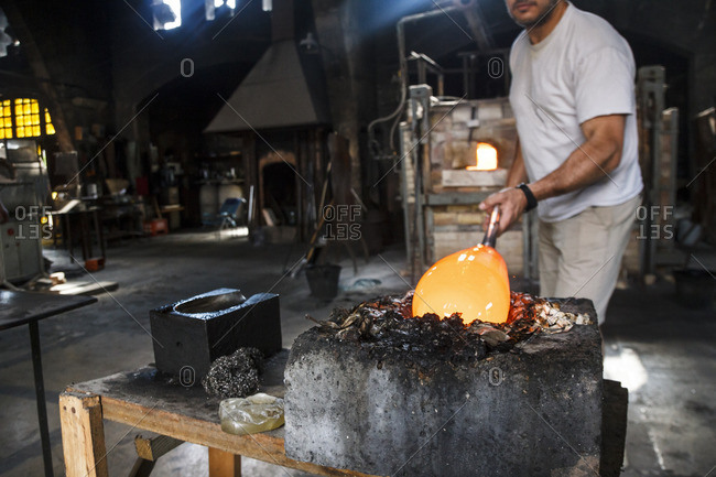 Man putting molten glass in a mold in a glass factory