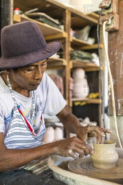 Potter in workshop working on earthenware jar