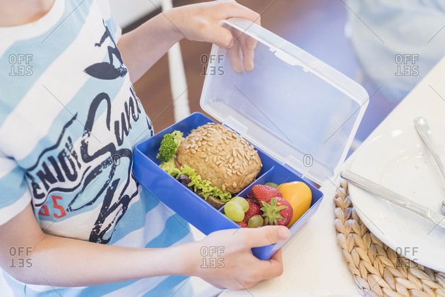 Boy packing lunch box with healthy food