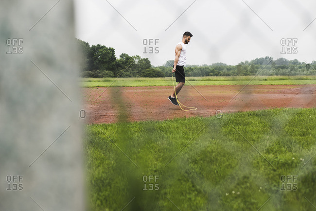 Athlete skipping rope on sports field