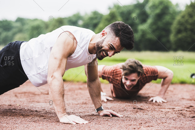 Two athletes doing pushups on sports field