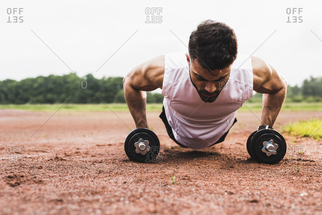 Athlete doing pushups with dumbbells on sports field