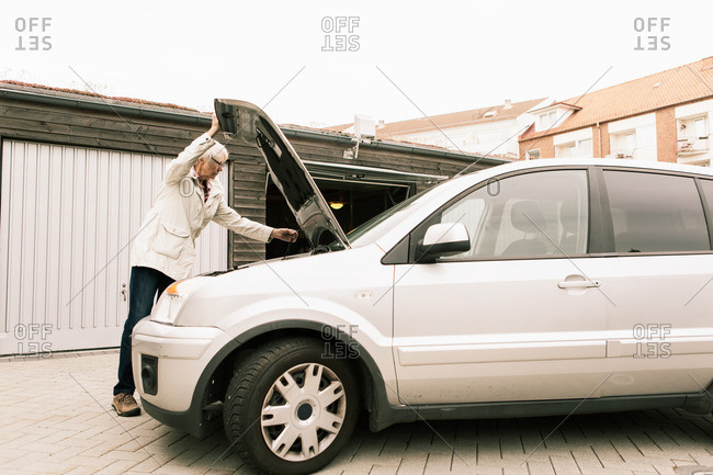 Ystad, Sweden - September 15, 2015: Senior woman opening car hood while standing by warehouse