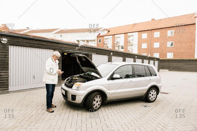 Ystad, Sweden - September 15, 2015: Senior woman using phone while standing by broken down car