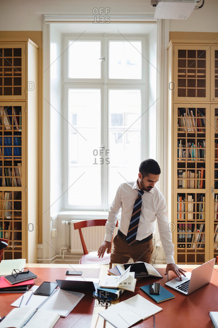 Lawyers using laptop while standing at table against window in library