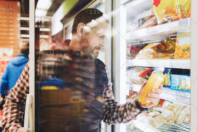 Male customer reading drink label seen through glass door at refrigerated section