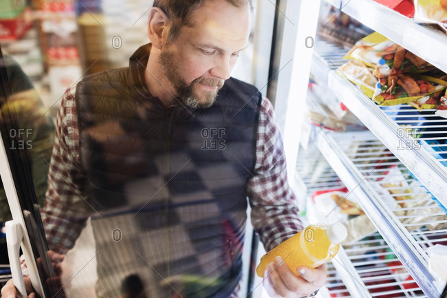 High angle view of male customer reading drink label at refrigerated section