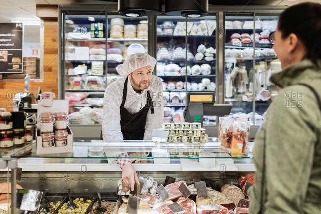 Sales clerk looking at female customer while assisting at supermarket