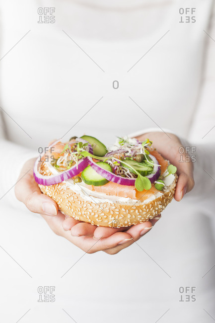 Woman holding a bagel with cucumber, onions, salmon and cream cheese