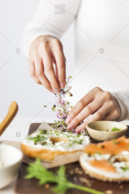 Woman preparing a bagel with cream cheese, salmon and sprouts