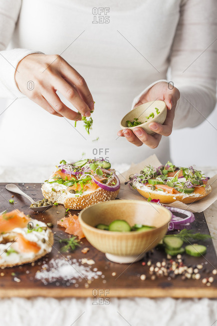 Woman assembling a bagel with cream cheese, salmon and fresh veggies