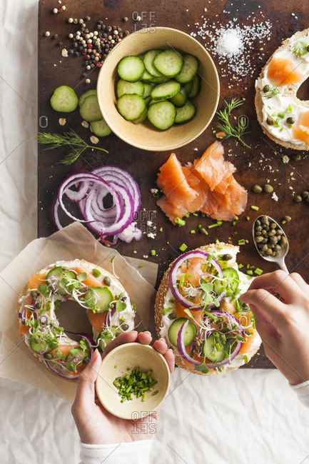 Hand of a woman putting together a bagel with cream cheese, salmon and fresh veggies